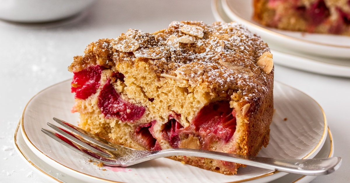 A wide shot of a closeup of a slice of rhubarb cake with a fork sitting next to it