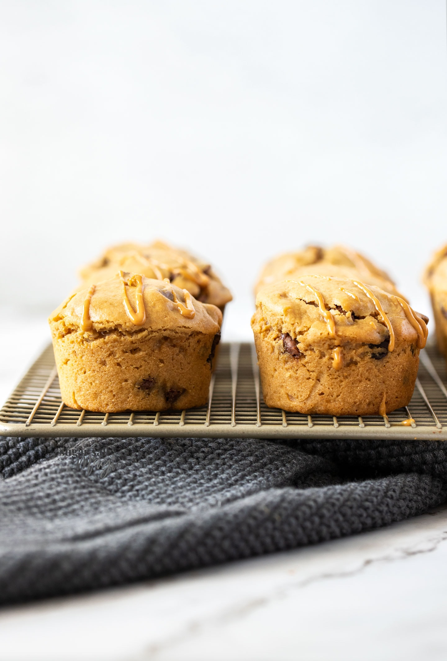 Muffins stacked side by side on a gold wire rack