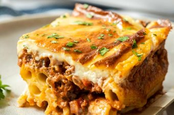 Closeup of a slice of pastitsio on a grey plate