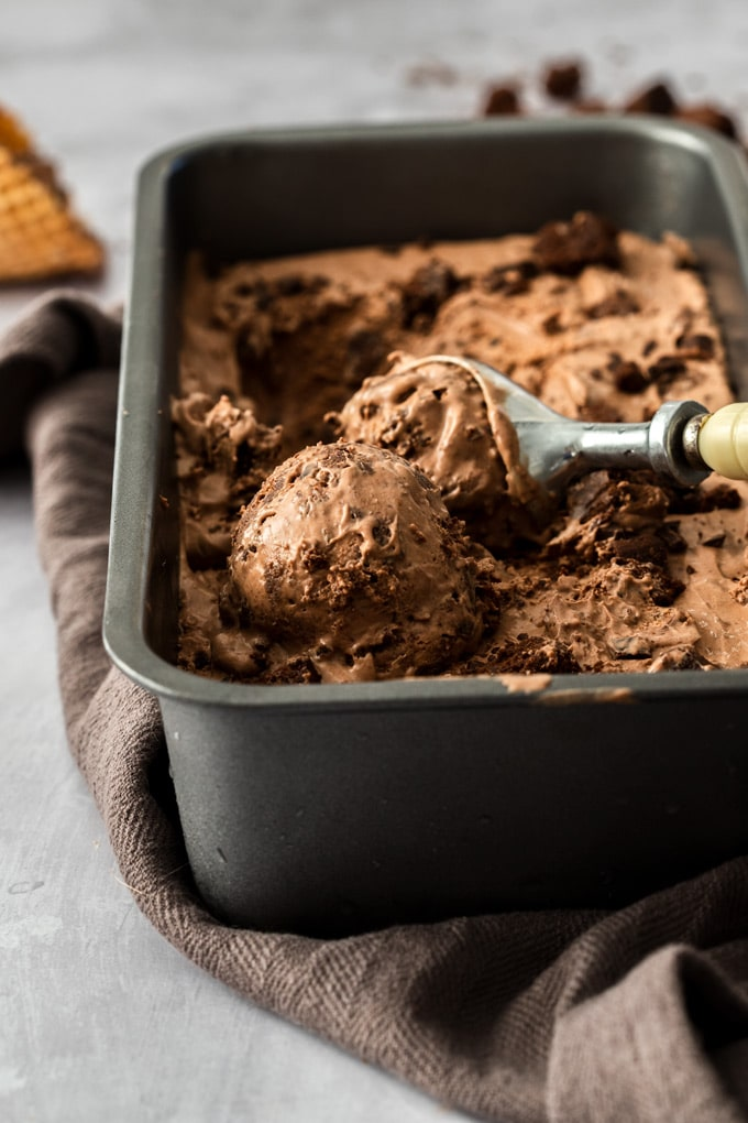 A loaf tin fill with chocolate brownie ice cream with a scoop in it