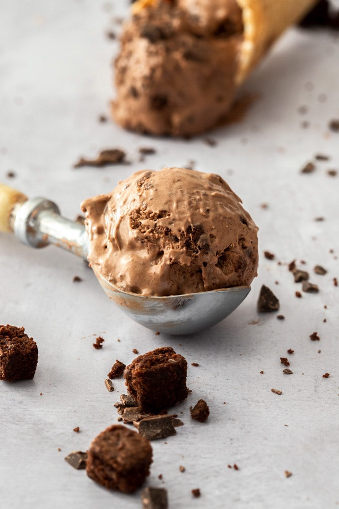 A scoop of chocolate ice cream still in the ice cream scoop