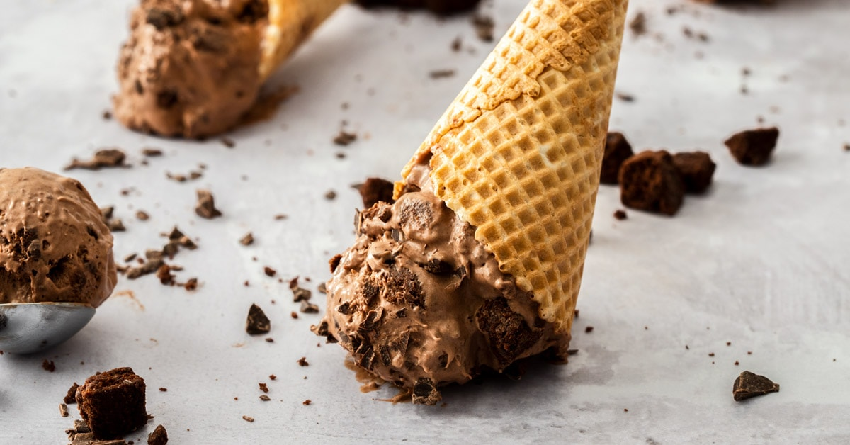 An upturned waffle cone filled with chocolate ice cream on a concrete bench top