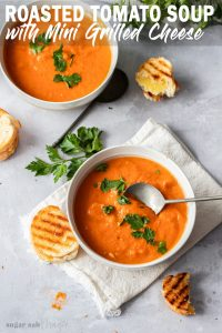 Overhead shot of two bowls of tomato soup with parsley and grilled cheese sandwiches nearby