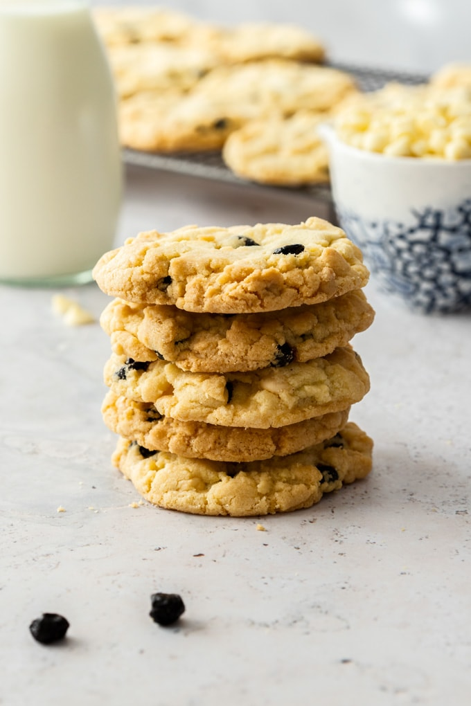 A stack of 5 cookies with more cookies on a cooling rack in the background and a bottle of milk