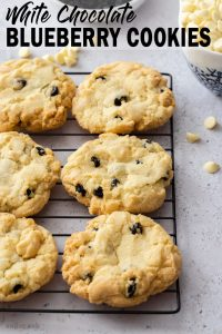 6 cookies sitting on a cooling rack on a grey surface with white choc chips around it