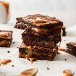 A stack of 3 Chocolate Caramel Brownies on a sheet of baking paper