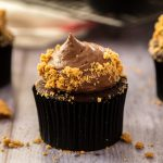 Closeup of a chocolate cheesecake cupcake with chocolate frosting, sprinkled with cookie crumbs. It sits on a grey wood surface