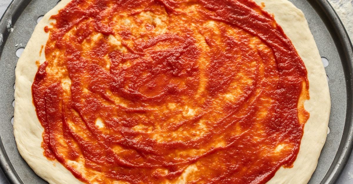 Close up of a pizza base spread with tomato paste