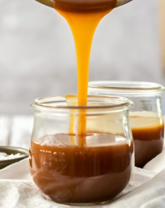 Caramel sauce being poured from a saucepan into a glass jar. Another sits behind
