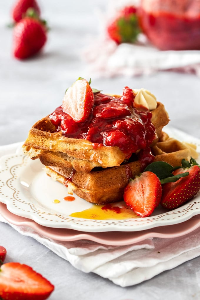 A stack of waffles on a white plate topped with strawberry compote