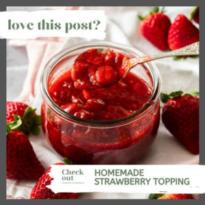 A spoon digging into strawberry topping in a round glass jar on a white napkin with strawberries around it