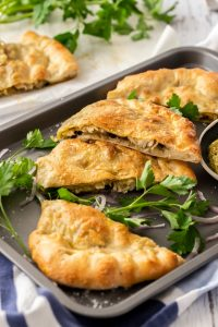 Slices of calzone on a grey baking tray surrounded by parsley and onion.