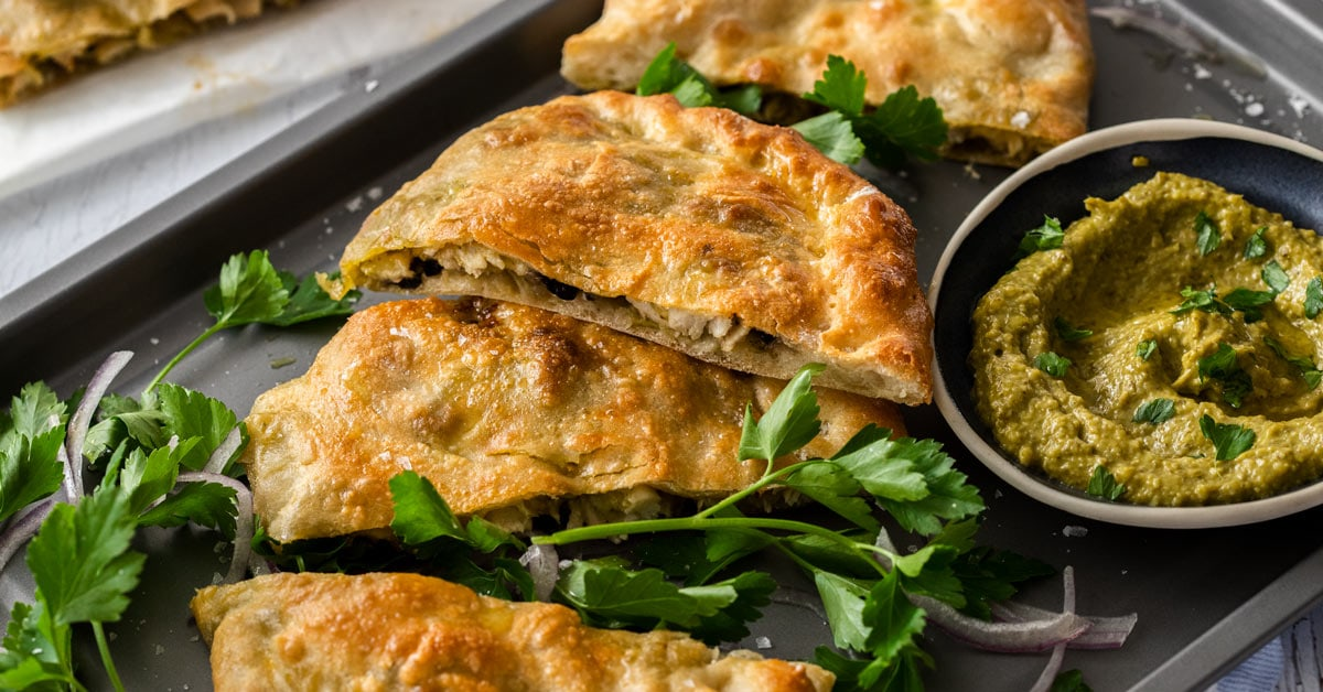 Slices of pesto chicken calzone on a grey baking tray next to a bowl of pesto