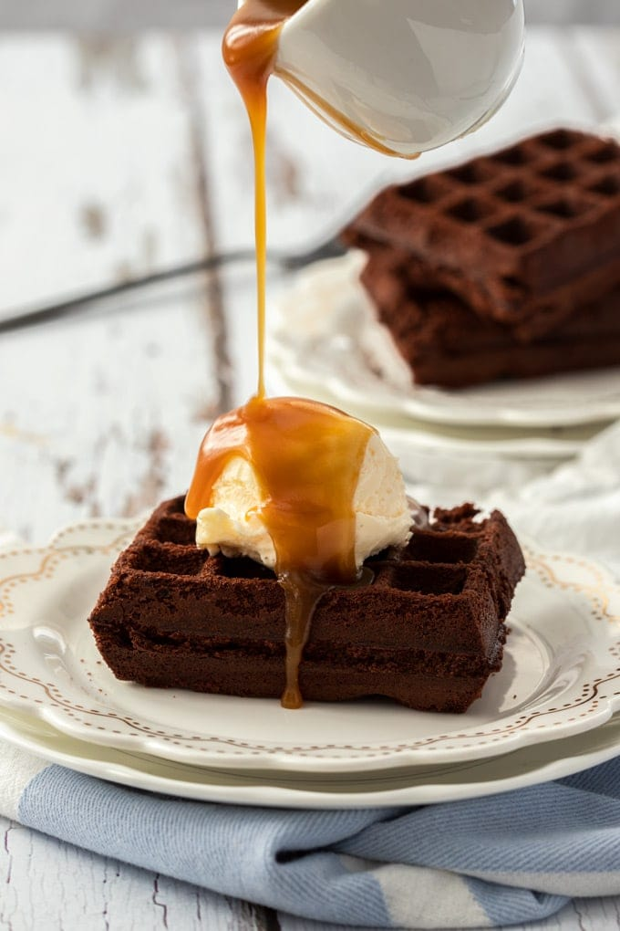 A waffle brownie topped with ice cream having caramel sauce drizzled over.