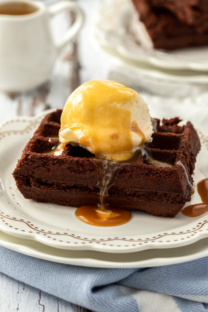 Closeup of a waffle brownie topped with ice cream and caramel sauce. Sitting on a white plate