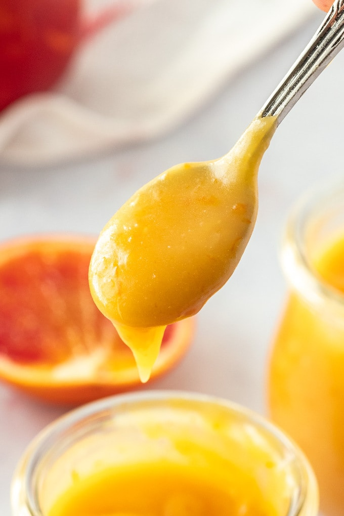 Closeup of a spoon with orange curd dripping off