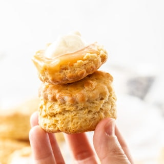 Two scones being held up by a hand