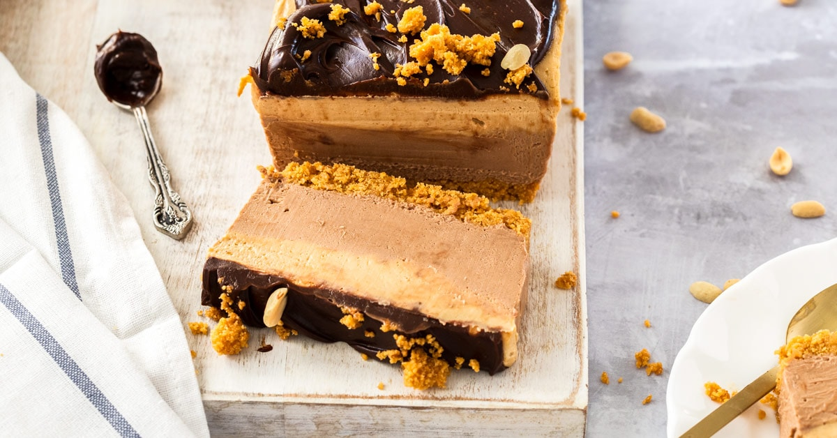 A rectangle peanut butter chocolate cheesecake with a slice laying in front of it, sitting on a white board