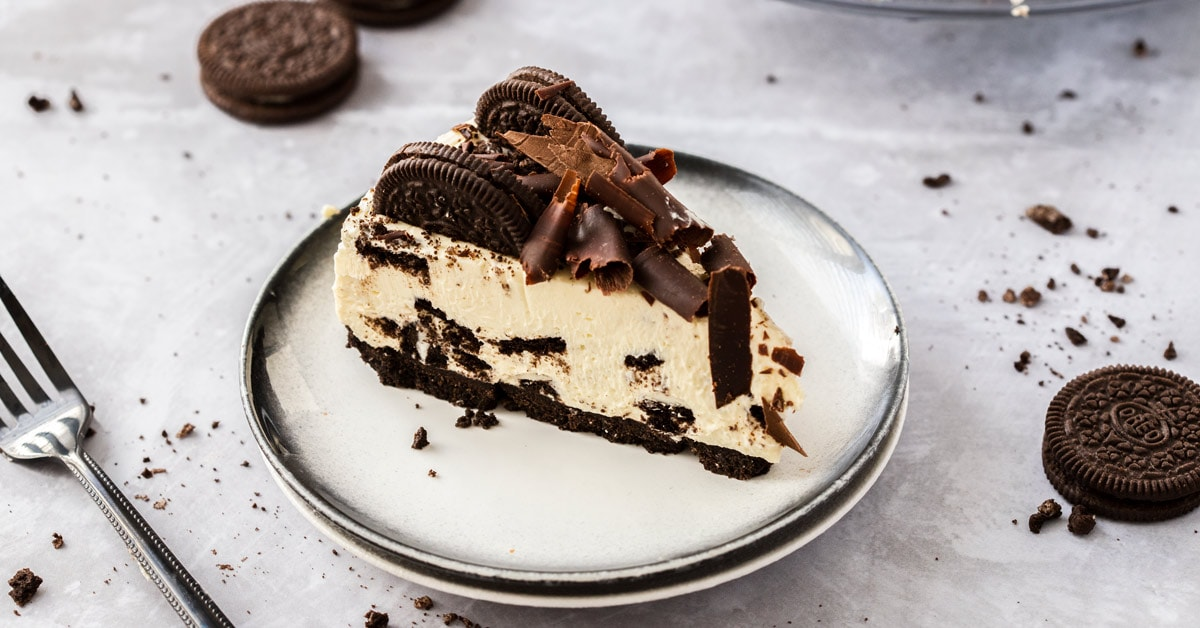 A slice of no bake oreo cheesecake on a white plate with oreos and crumbs strewn around. a black fork in front