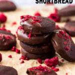 A stack of dark chocolate shortbread cookies, sprinkled with freeze-dried raspberries on a sheet of brown baking paper