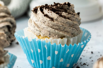 Closeup of a cupcake in a blue polka dot wrapper, topped with oreo buttercream