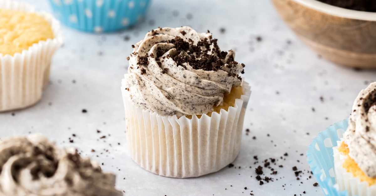 A cupcake in a white wrapper with oreo buttercream and topped with oreo crumbs.