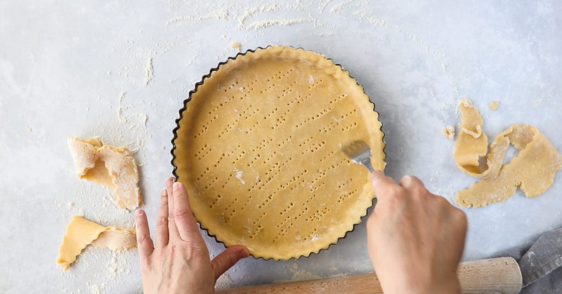 A fork being used to prick holes in the base of a pastry tart shell