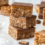 A stack of 3 snickers rice krispie treats on a sheet of white baking paper