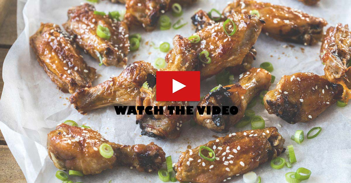 A batch of chicken wings with a sticky coating. Text on the image says to watch the video.