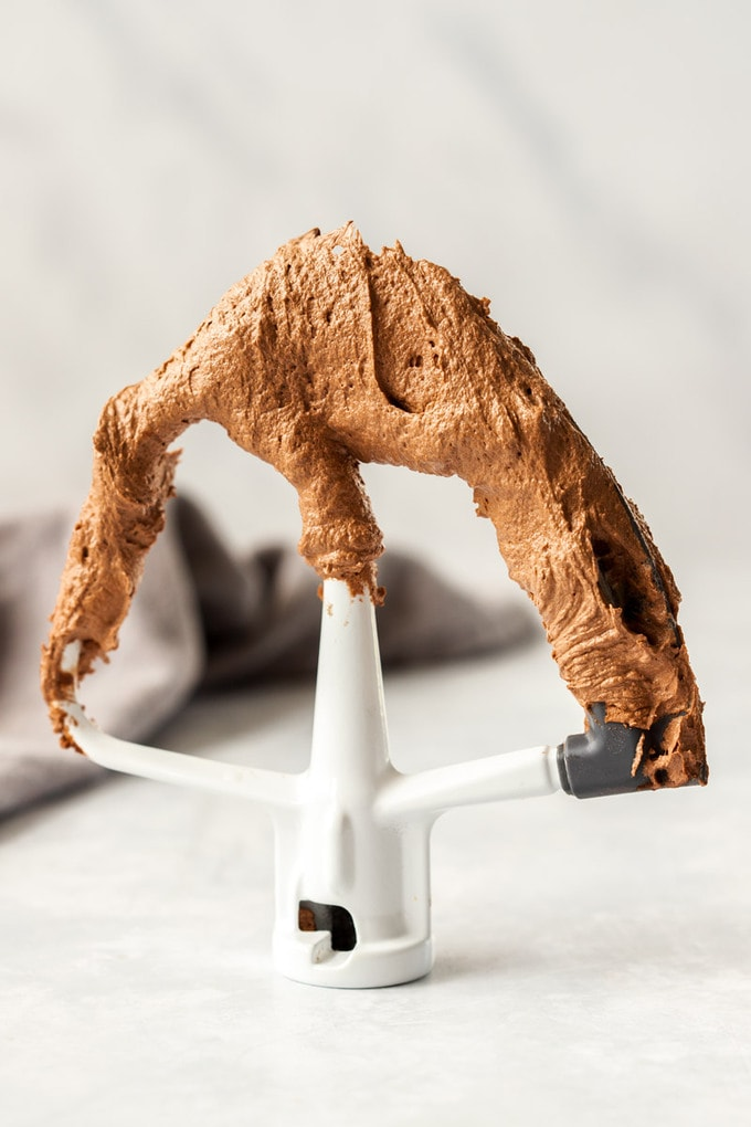 The paddle attachment from a stand mixer covered in chocolate frosting and standin gup on a bench top