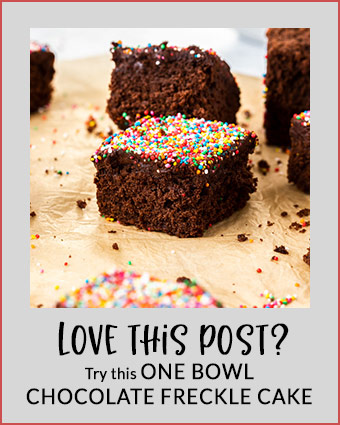 3 square slices of chocolate cake topped with sprinkles in lined up on a piece of brown parchment paper