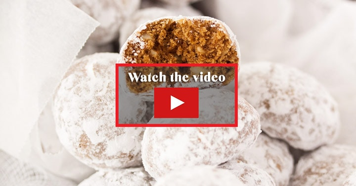A sugar dusted gingerbread snowball cookie sitting on top of a pile of them. This is a link to watch the video