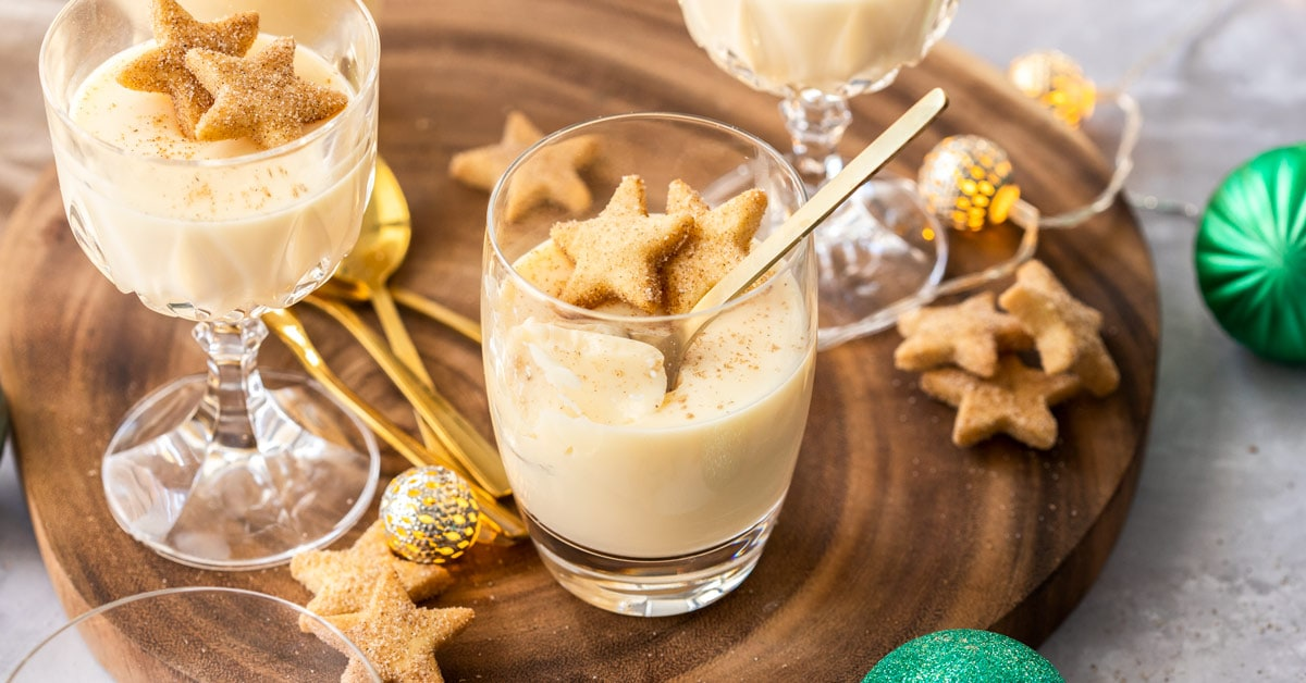 Glasses filled with eggnog panna cotta on a wooden board, surrounded by shortbread and festive ornaments.
