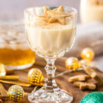 A goblet filled with eggnog panna cotta on a wooden board, surrounded by shortbread and festive ornaments