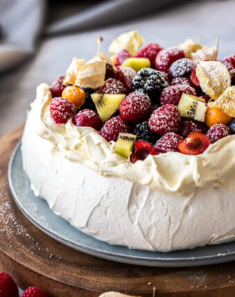 Close up of a pavlova toppedw with whipped cream and fruit on a wooden platter