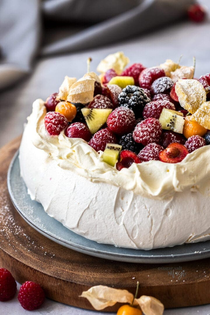 Close up of a pavlova toppedw with whipped cream and fruit on a wooden platter.