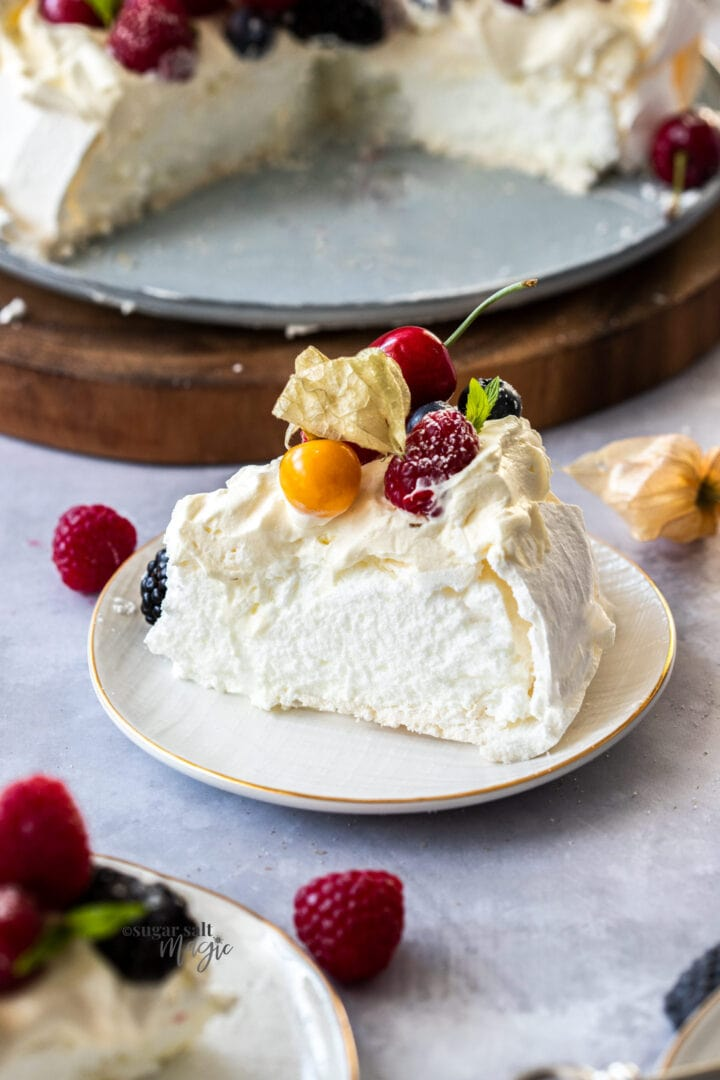 A slice of pavlova on a small whtie plate with berries on top.