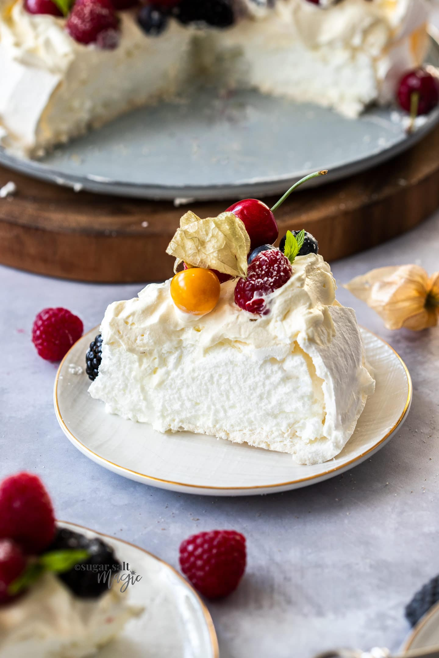 A slice of pavlova on a small whtie plate with berries on top