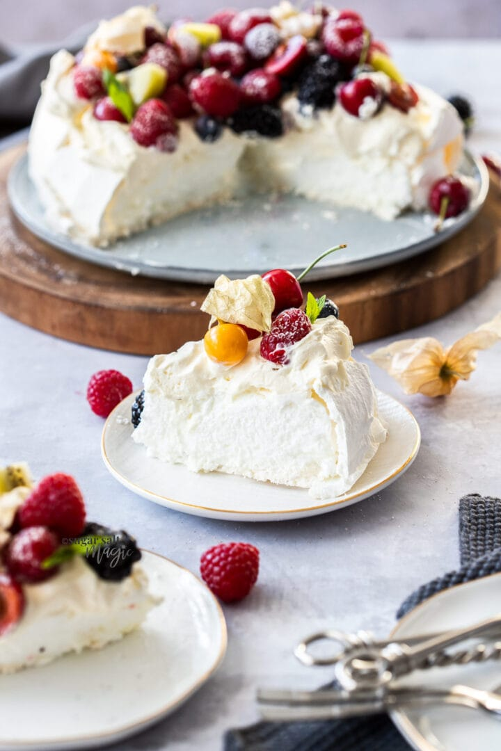 A slice of pavlova topped with fresh cream and berries on a white plate. The rest of the pavlova sits in the background.