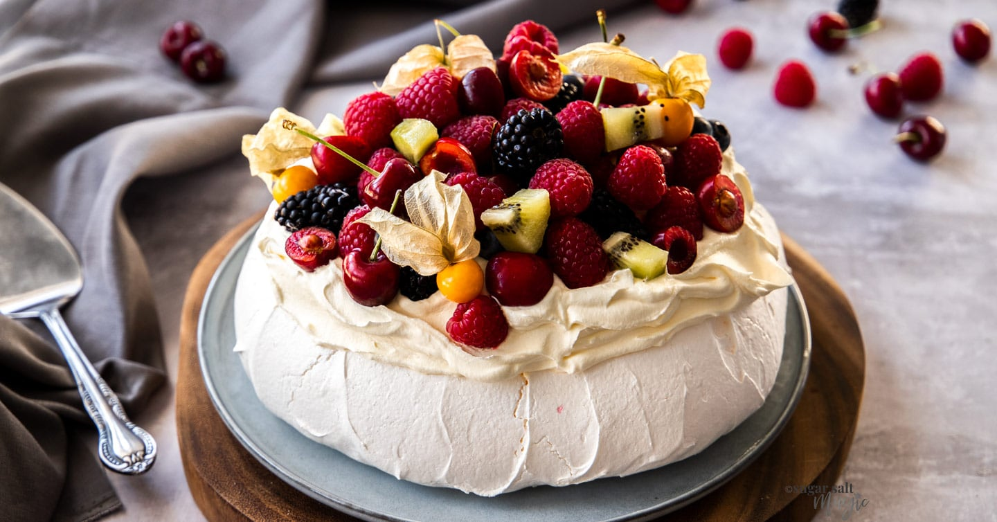 A pavlova topped with fresh cream and berries on a wooden platter