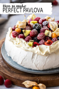 Close up of a pavlova topped with whipped cream and fruit on a wooden platter