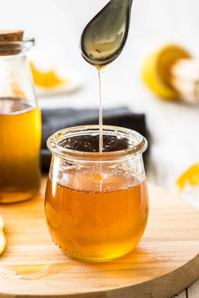 Lemon syrup drizzling off a spoon into a jar.