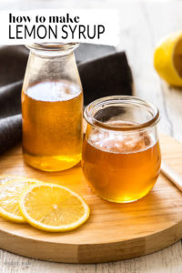 A jar and bottle both filled with lemon syrup, sitting on a wooden board.