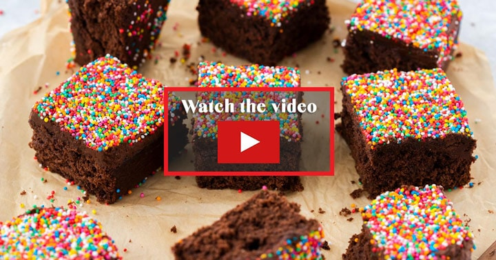 9 square slices of chocolate cake topped with sprinkles on a piece of brown parchment paper. In the middle it says watch the video