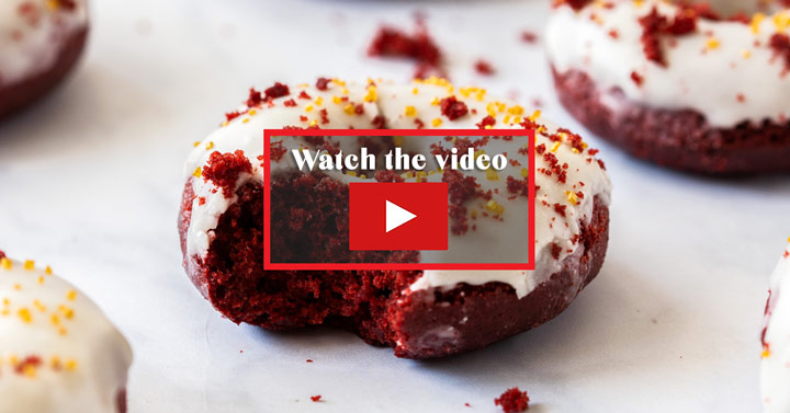 "A red velvet donut with a bite taken out of it. In the centre it says ""watch the video"""