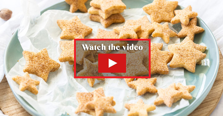 "A pastel green plate topped with star shaped shortbread cookies. A note in the middle says ""Watch the video"""