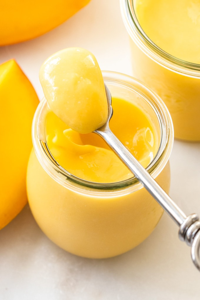 A spoon filled with curd sitting on top of a jar filled with mango curd
