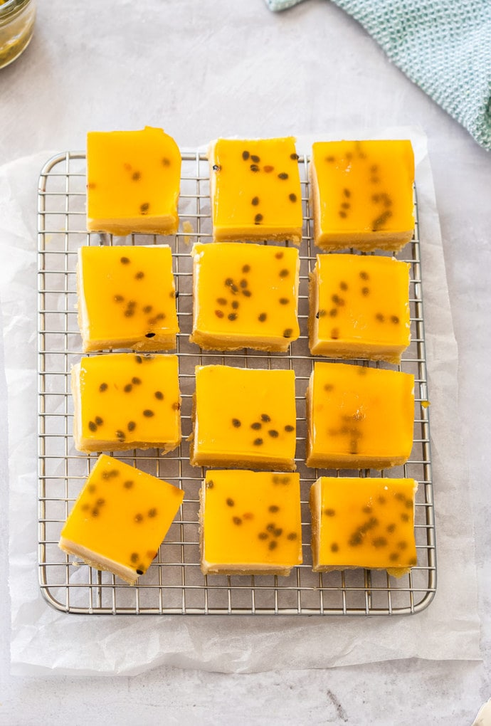 Pieces of passionfruit slice lined up on a wire rack