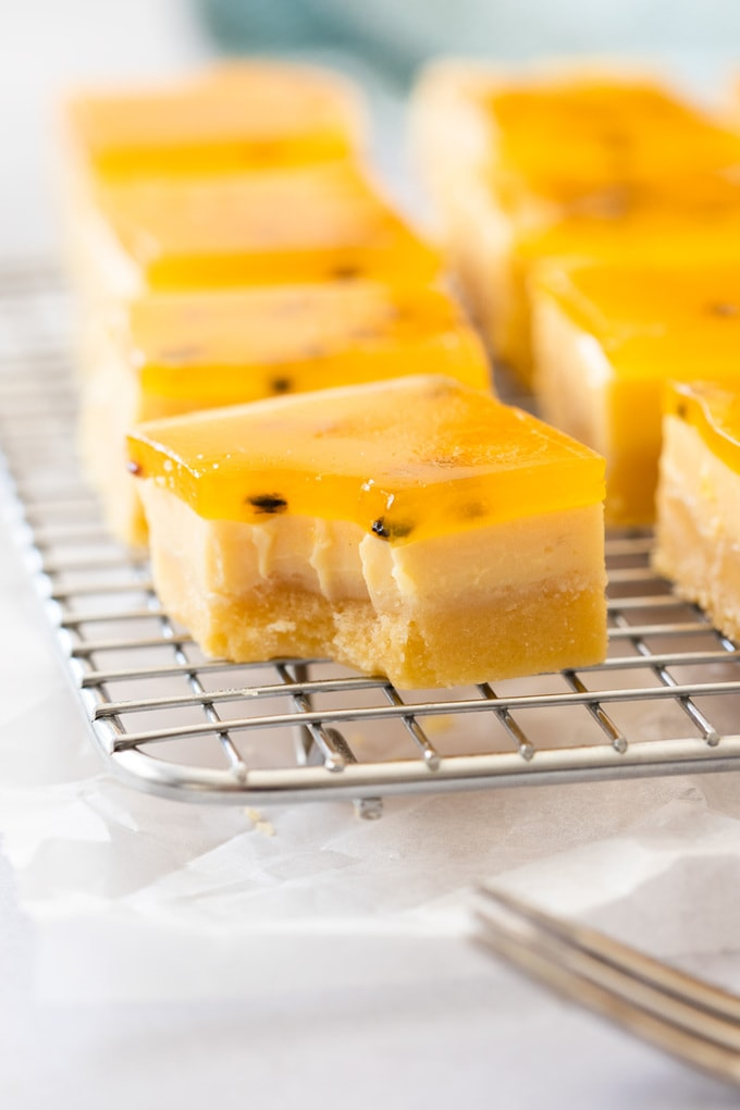 A piece of passionfruit slice with a bite taken out of it, sitting on a wire rack