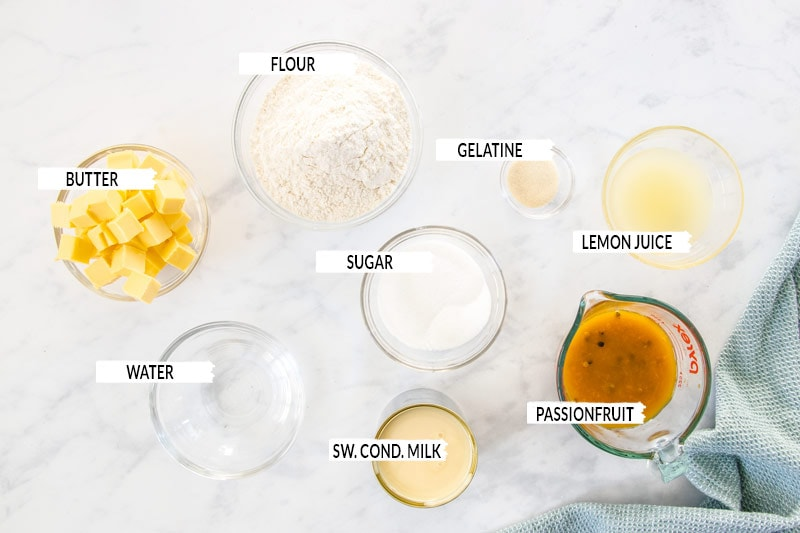 Ingredients for passionfruit slice laid out in small bowls on a marble surface